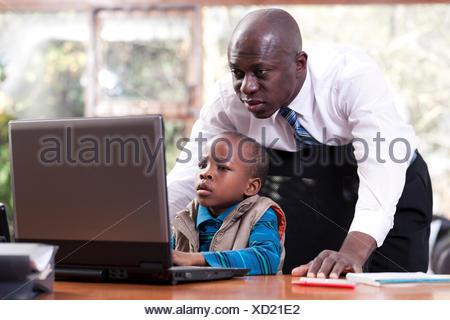 Un giovane ragazzo africano si siede a suo padre la scrivania, giocando su un leptop mentre suo padre veglia sulla sua spalla Foto Stock