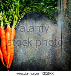 Le carote fresche mazzetto su legno Foto Stock