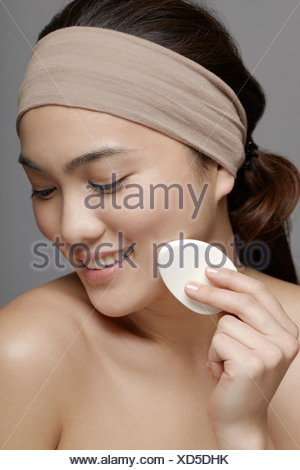 Giovane donna usando make up spugna Foto Stock