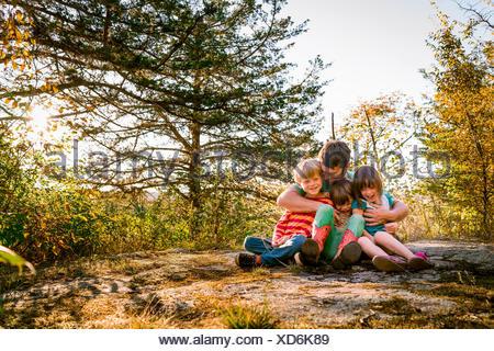 Padre seduto nella foresta che abbraccia tre bambini Foto Stock