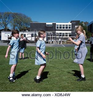 Scolare il salto nel parco giochi della scuola primaria Isola di Man Regno Unito Foto Stock