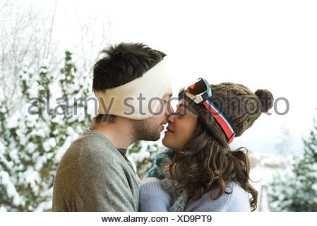 Coppia giovane in abbigliamento invernale, baciare, vista laterale Foto Stock