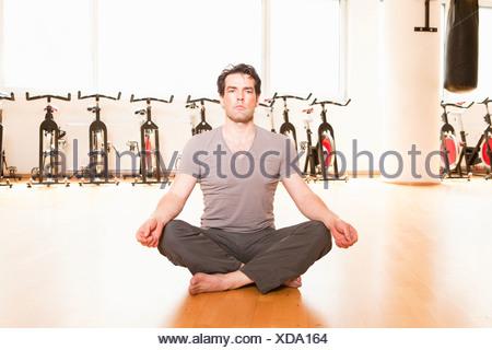 L'uomo meditando sul tappetino in palestra Foto Stock