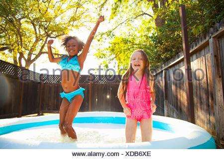Due ragazze jumping in giardino piscina per bambini Foto Stock