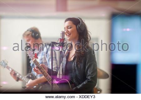 Giovani band che suona musica in studio di registrazione Foto Stock