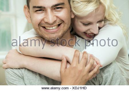 Giovane donna abbracciando il fidanzato Foto Stock