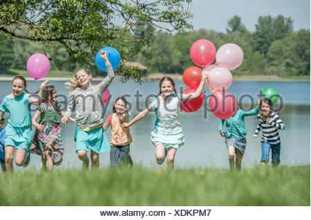 I bambini in esecuzione nel parco con palloncini, Monaco di Baviera, Germania Foto Stock