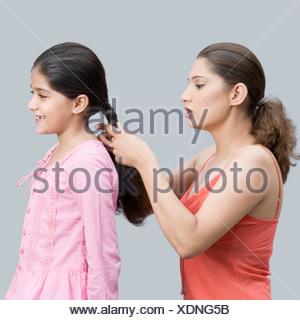 Profilo laterale di una giovane donna un intreccio di sua figlia i capelli Foto Stock