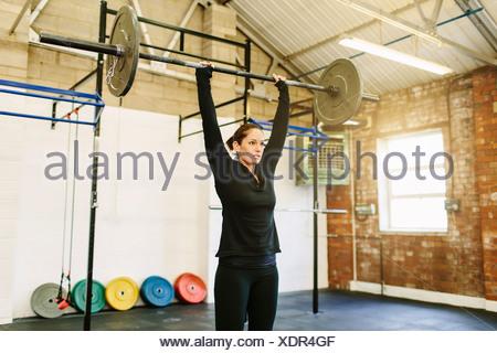 Sollevamento donna barbell in palestra Foto Stock