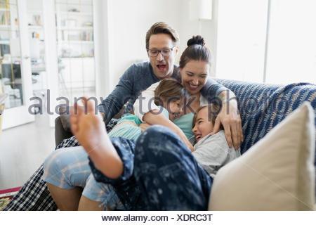 Famiglia giocoso in pigiama solletico sul divano Foto Stock