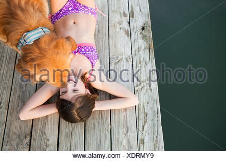 Una giovane ragazza e un golden retriever cane su un molo. Foto Stock