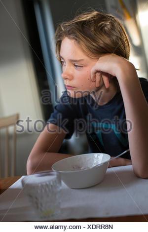 La Svezia, ragazzo (14-15) seduta a tavola con la coppa e il vetro Foto Stock