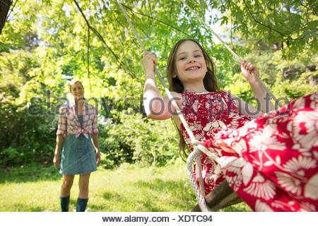 L'estate. Una ragazza in un sundress su altalena sotto un albero frondoso. Una donna in piedi dietro di lei. Foto Stock