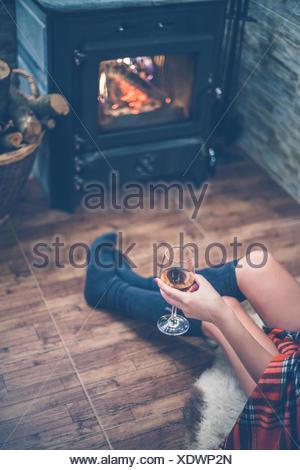 Vista in elevazione della donna seduta davanti a una stufa a legna con un bicchiere di vino in mano Foto Stock
