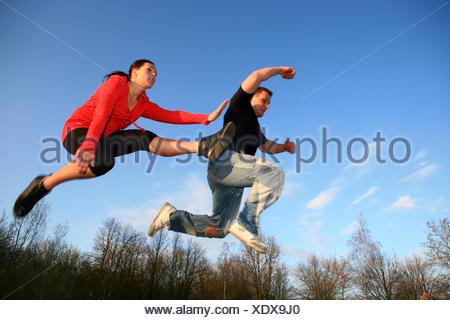 Il giovane e la giovane donna il salto, Germania Foto Stock