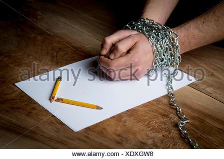 Giovane uomo con catene avvolte attorno ai suoi polsi, carta e matita rotta davanti a lui, concentrarsi sulle mani Foto Stock