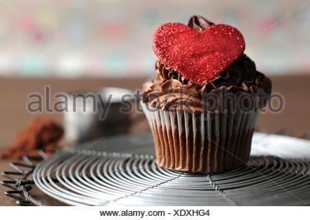 Tortina di cioccolato con zucchero rosso cuore sulla parte superiore Foto Stock