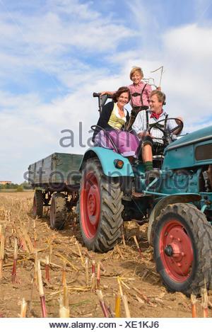 La famiglia sul trattore in cornfield, Baviera, Germania Foto Stock