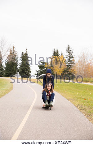 Le ragazze del Tween skateboard sul percorso in autunno park Foto Stock