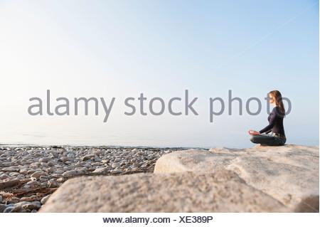 Giovane donna nella posizione del loto seduto sulla roccia a costa Foto Stock