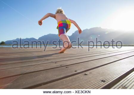 Ragazzo in esecuzione a saltare in un lago da un pontile Foto Stock