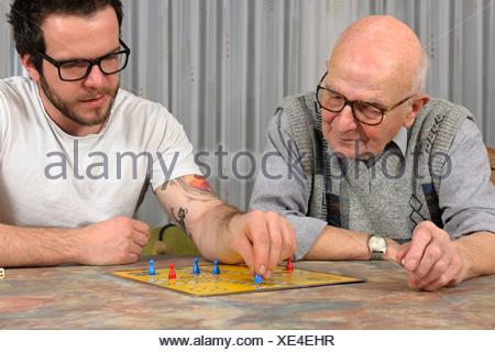 Nonno e nipote giocare insieme ludo a casa Foto Stock
