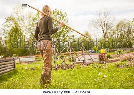 Donna matura, all'aperto, giardinaggio, portando rastrello, vista posteriore Foto Stock