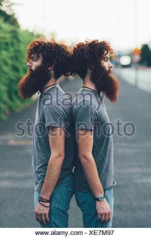 Ritratto di identico maschio adulto gemelli con i capelli rossi e le barbe di schiena sul marciapiede Foto Stock