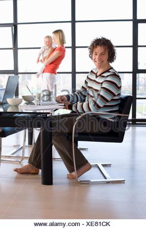 Uomo seduto al tavolo da pranzo, sorridente, ritratto, madre tenendo la nostra bambina da una finestra in background Foto Stock