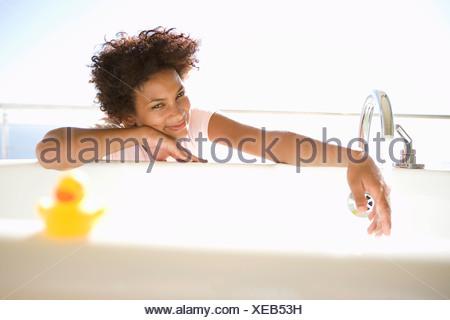 Giovane donna seduta da bagno, sorridente, rubber duck in primo piano Foto Stock