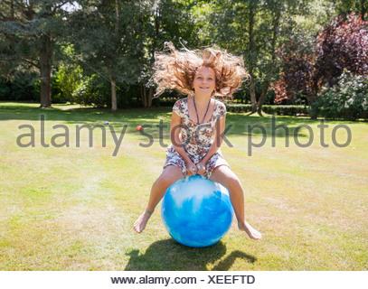 Ragazza saltando su Space Hopper Foto Stock