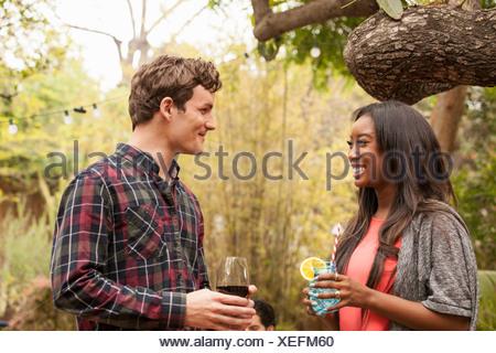 Amici con bevande al barbecue nel cortile Foto Stock