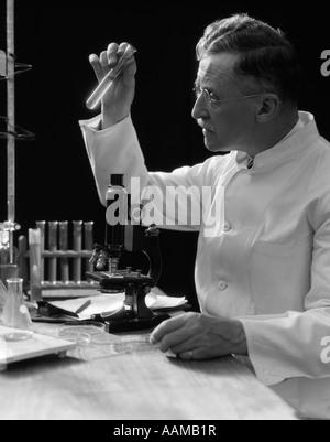 1920 1930 1940 CIENTISTA LABORATÓRIO TÉCNICO NO AVENTAL BRANCO OLHANDO PARA TUBO DE ENSAIO NA FRENTE DO microscópio Foto de Stock