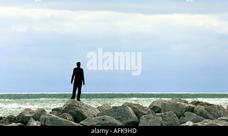 Silhueta da jovem sobre rochas no lago permanente do Lago Michigan Foto de Stock