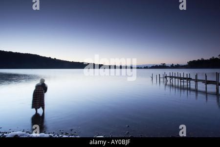 Homem lavagem no lago ao amanhecer, Bali Foto de Stock