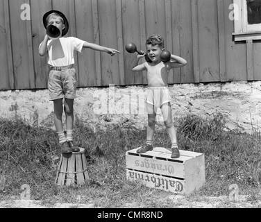 1930 1940 rapazes que jogavam CARNAVAL homem forte um levantamento HALTERES OUTROS anunciando actuar através de Foto de Stock