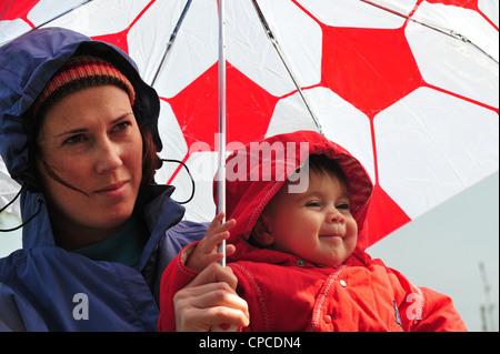 A mãe e o bebé fique sob um guarda-sol e olhar para a queda de chuva em um dia de inverno . Foto de Stock