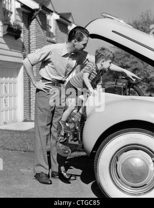1940 PAI & FILHO VERIFICAR SOB O CAPÔ DO carro na garagem Foto de Stock