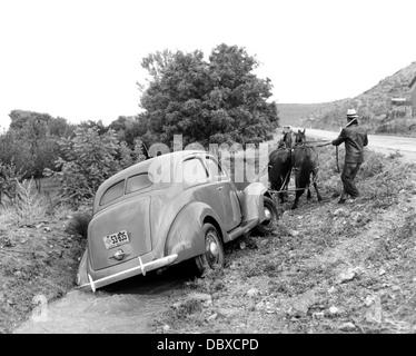 1930 1937 FORD V-8 SENDO PUXADO PARA FORA DA ESTRADA RURAL VALA pelo homem com a equipe de dois cavalos Foto de Stock