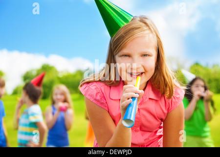 Retrato da menina com apito noisemaker feliz em uma festa de aniversário de gorro com amigos no fundo permanente Foto de Stock