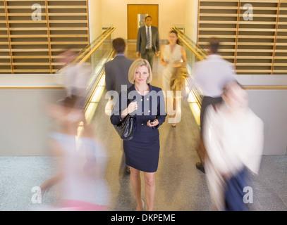 Empresária andando no corredor de escritório ocupado Foto de Stock