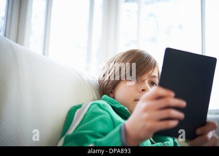Rapaz no sofá usando tablet digital Foto de Stock