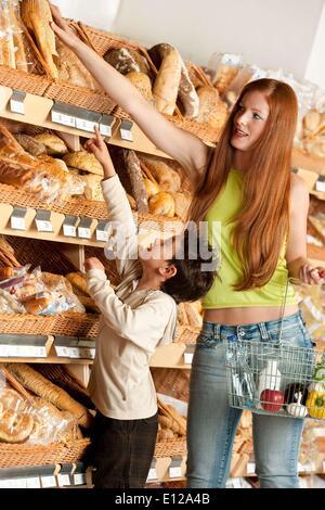 15 de Maio de 2009 - 15 de Maio de 2009 - Supermercado compras - cabelo vermelho mulher e criança escolhendo o pão Foto de Stock