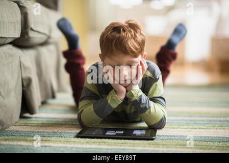 Boy (6-7) deitado sobre o tapete e usando o tablet pc Foto de Stock