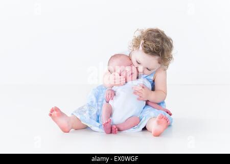 Doce menina toddler beijar seu bebê recém-nascido irmão Foto de Stock