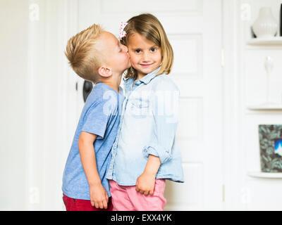 Little boy (4-5) beijar a irmã (4-5) Foto de Stock