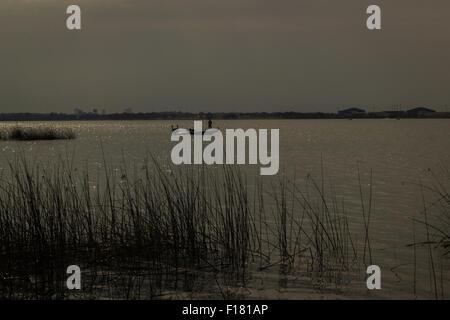 Silhouette o homem no barco no lago Foto de Stock