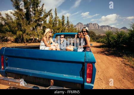 Grupo de amigos sentados na parte de trás de um carro pick-up. Homens e mulheres jovens indo em uma viagem na natureza. Foto de Stock