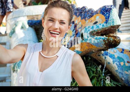Obtenha inspirado pelo Parque Guell em sua próxima viagem a Barcelona, Espanha. A sorrir jovem mulher tendo selfie Foto de Stock