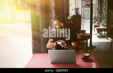 Jovem Empresário barbudo vestindo Preto Tshirt Trabalhando Laptop Urban Cafe.Homem sentado mesa de madeira chávena Foto de Stock